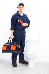 Plumber poses with equipment and toilet